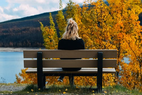 Back view of unrecognizable female sitting on wooden bench and admiring picturesque scenery of river near green hill in autumn time