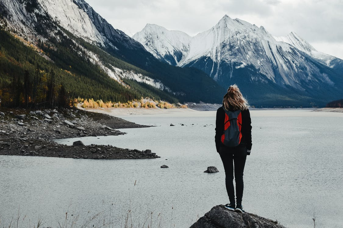 Traveler admiring lake surrounded by snowy mountains