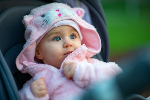 Little girl sitting in stroller on playground