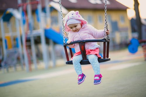 Cheerful little girl riding on swings