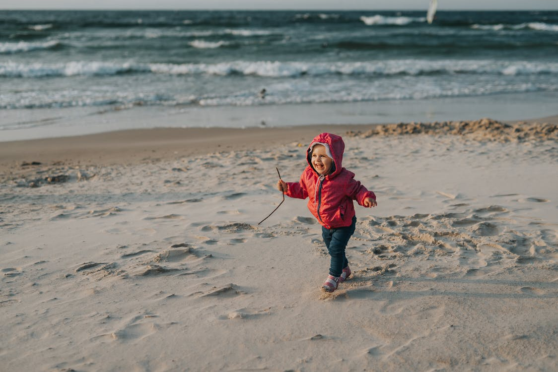 Funny little girl playing on beach