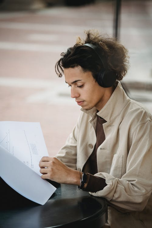 Young ethnic male in casual clothes and headphones sitting in street at table and reading papers in daytime