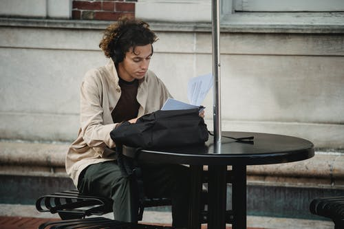 Concentrated young ethnic guy in casual outfit and earphones sitting at table on bench in street and studying papers near backpack in daylight