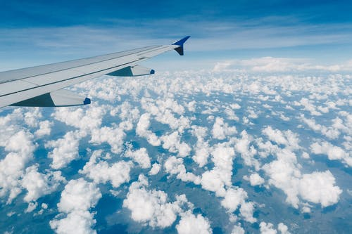 Aerial view of modern metal airplane wing in blue sky over fluffy clouds