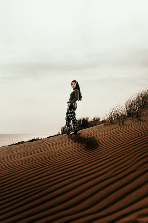 Woman in White Long Sleeve Shirt and Black Skirt Standing on Brown Sand Near Body of during