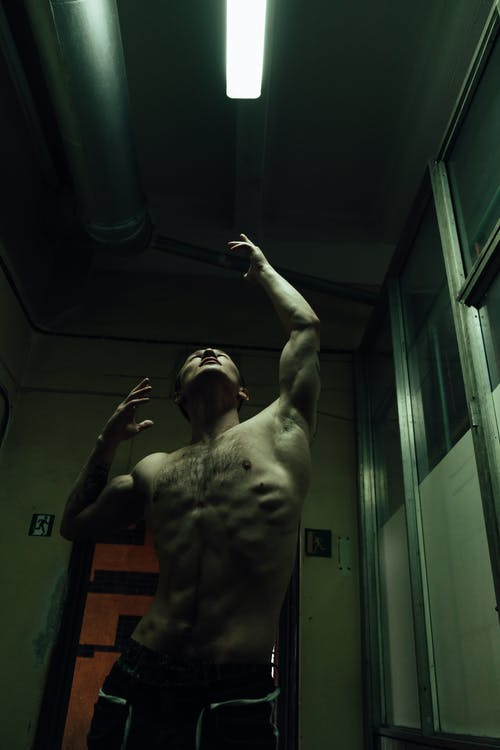 From below of shirtless fit male reaching for flashlight while looking up in abandoned building