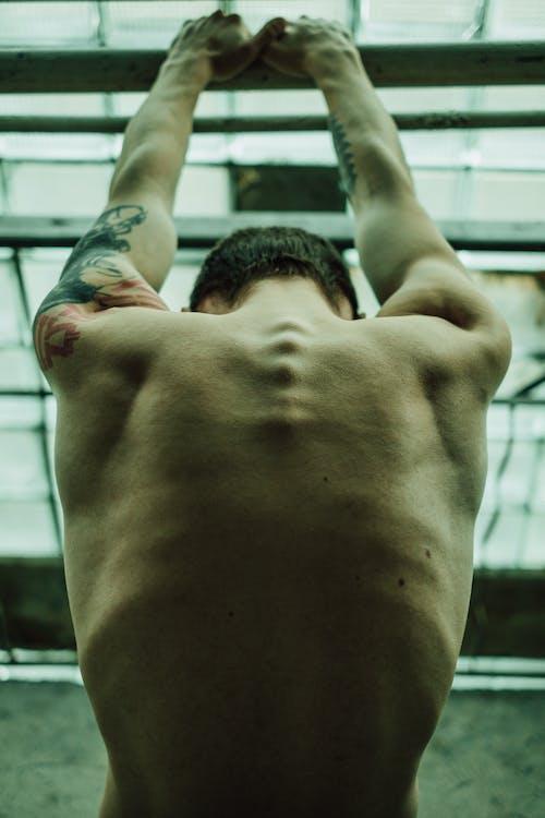 Strong shirtless man hanging on metal bar