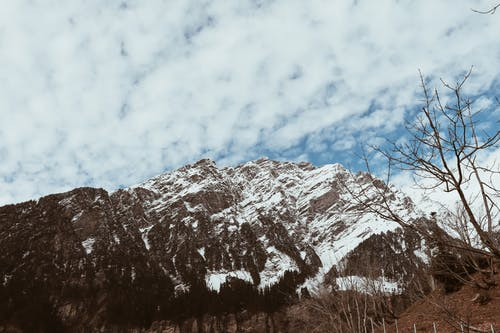 Picturesque view of snowy mountain range near hill with leafless trees under blue cloudy sky