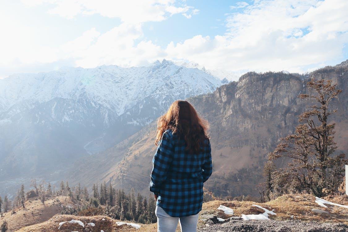 Unrecognizable woman standing on mountain peak
