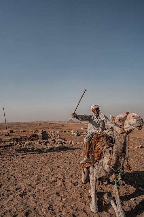 Man in Brown Robe Riding Camel