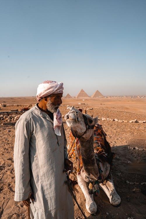 Man in White Thobe Riding Camel