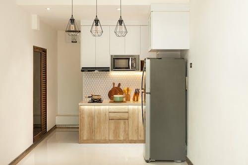 Gray Top Mount Refrigerator Beside Brown Wooden Kitchen Cabinet