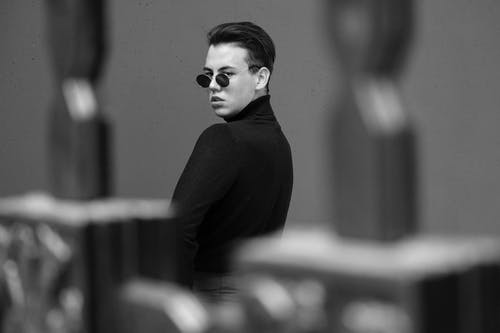Black and white trendy arrogant male in black turtleneck and sunglasses standing behind balustrade and looking at camera over shoulder with attitude