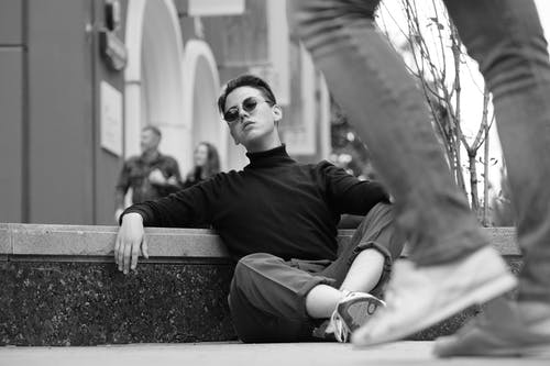 Black and white young arrogant male in stylish clothes and sunglasses sitting confidently on road curb on street and looking at camera with challenging glance