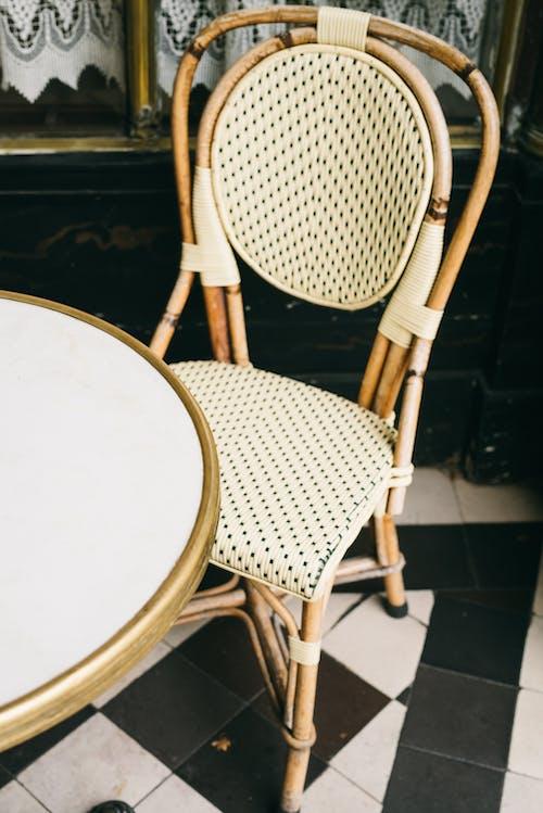 Коричневый деревянный стул рядом с белым круглым столом