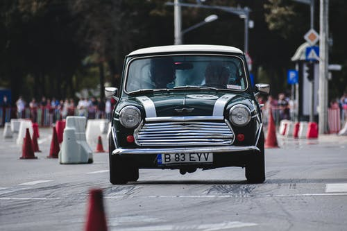 Unrecognizable driver riding classic racing automobile on asphalt track with traffic cones in city