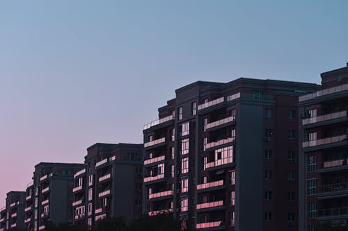 Facades of residential buildings with modern glass balconies at sunset