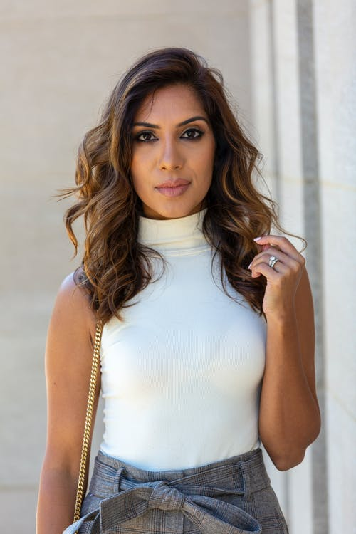 Young female with wavy hair in classy outfit looking at camera near gray wall of building