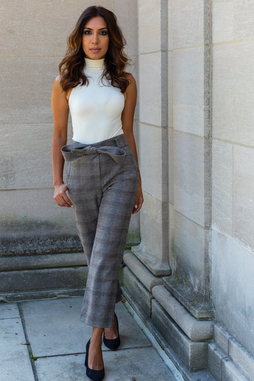 Young woman in stylish checkered trousers near gray wall