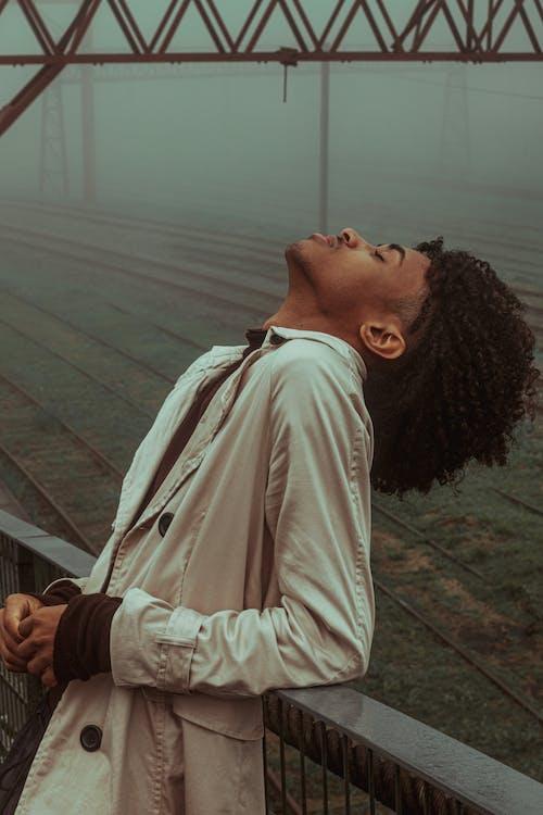 Black man standing on bridge near railways in foggy weather