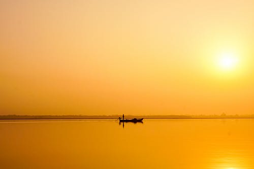 Silhouette of Person Riding Boat on Calm Sea during Sunset