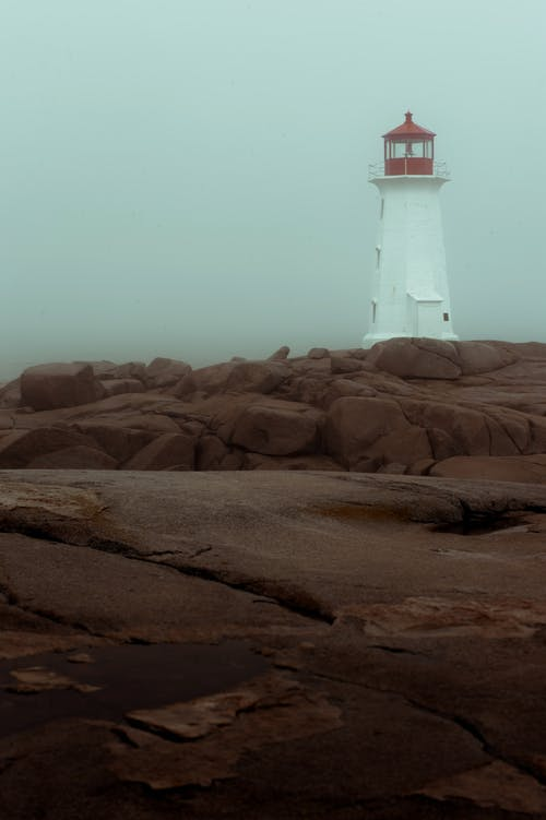 White and Red Lighthouse on Brown Sand
