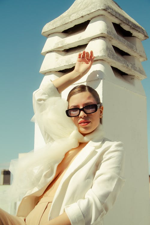 Stylish woman leaning on stone construction
