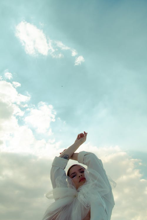 From below of graceful female in trendy outfit raising arms and looking at camera under cloudy sky
