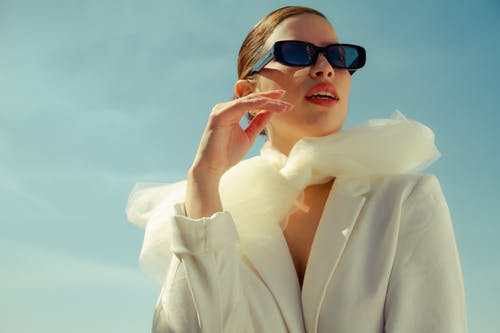 Low angle of stylish female model in sunglasses standing with opened mouth and looking away