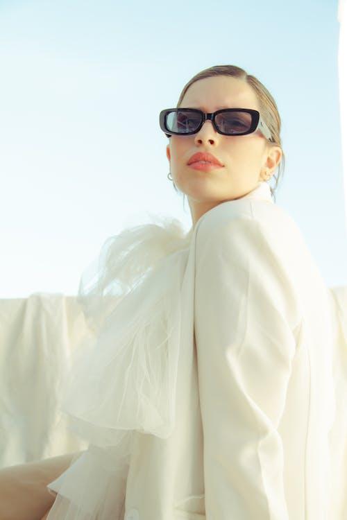 Stylish woman in sunglasses under blue sky