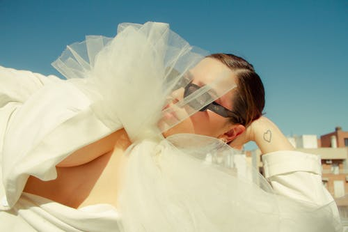 From below of elegant female in trendy outfit and sunglasses lying on roof under sunlight