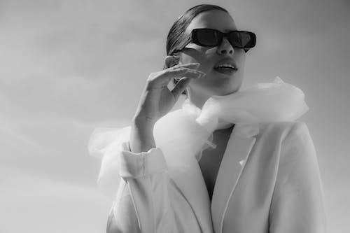 Stylish woman in sunglasses under sky