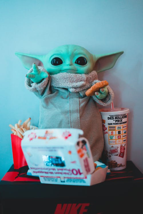 Plastic toy anime figure with chicken cutlet near fast food box and French fries at home