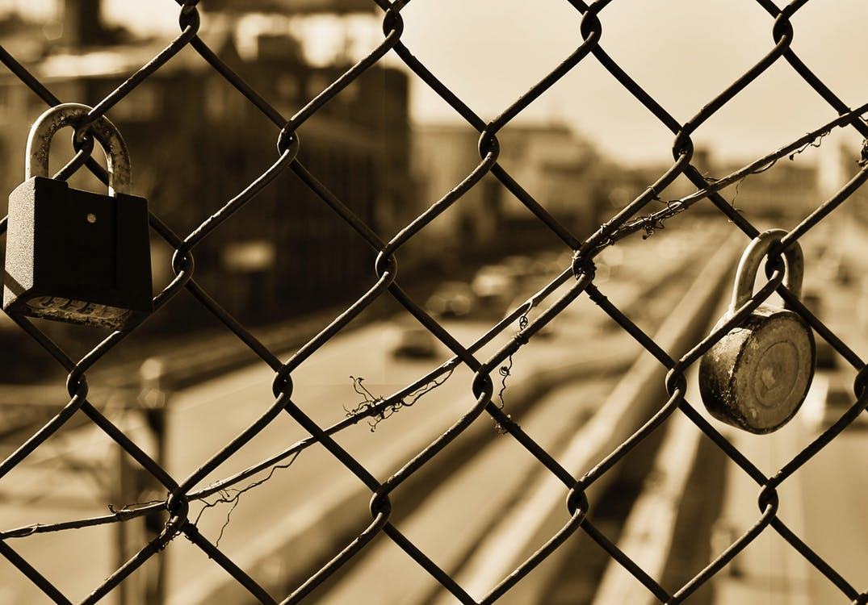 Two Black Padlocks on Grey Metal Wire Fence