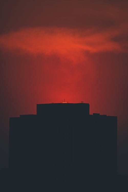 Silhouette of contemporary building located under red sky with floating cloud at sunset time in city in night in darkness