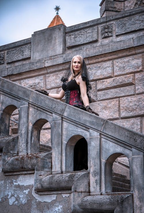 Woman in Black and Red Dress Sitting on Concrete Stairs