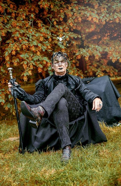 Man in Black Coat Sitting on Green Grass Field