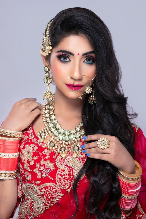 Indian female in traditional bridal clothes with makeup and jewelries
