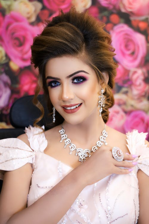 Smiling female in elegant dress and makeup with accessories