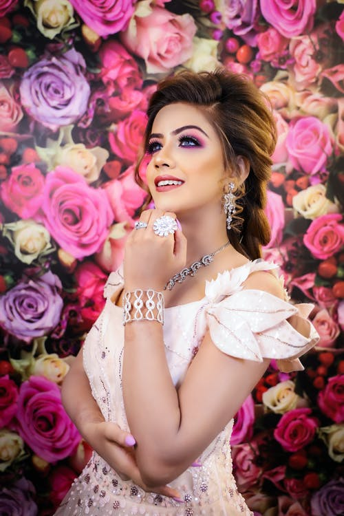 Dreamy young woman in pink dress with hairdo in makeup with earrings and necklace with rings and bracelet looking away happily near wallpapers covered with roses