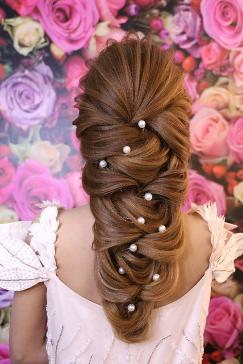 Back view of unrecognizable lady in pink dress with hairdo and head accessories near wallpapers covered with roses