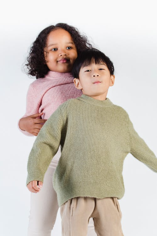 Cute multiracial children standing together in white studio