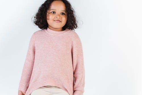 Cute black girl in soft knitted sweater in studio