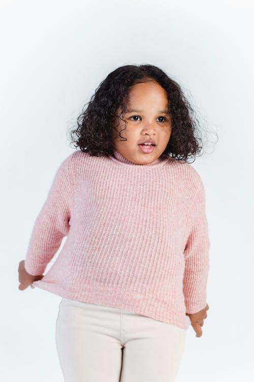 Adorable black little girl standing against white background