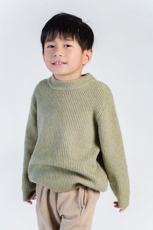 Cute ethnic boy in knitted wear in studio