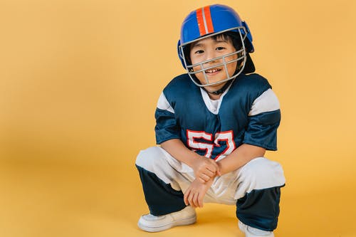 Smiling ethnic boy in helmet and uniform of football player