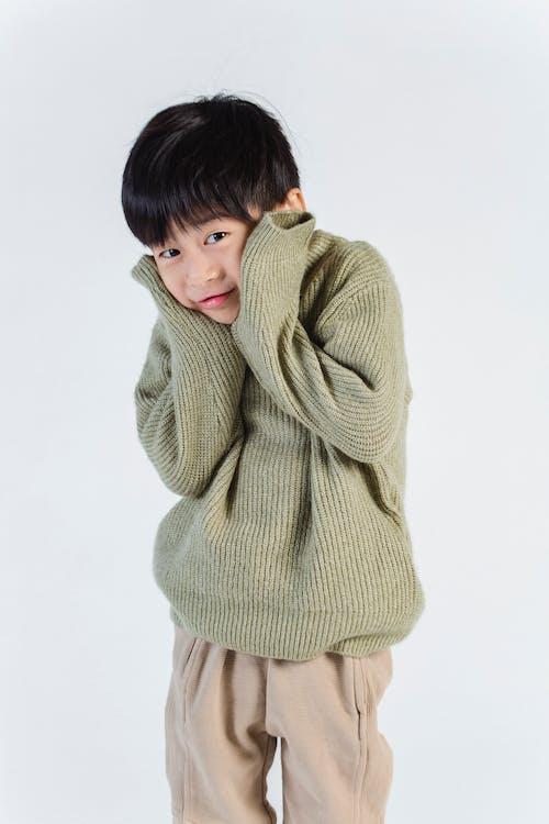 Cute shy ethnic boy in sweater