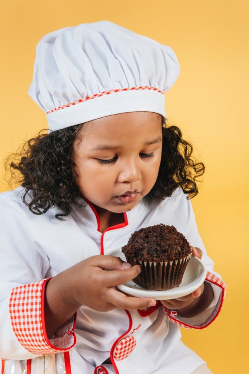 From above of African American girl wearing cook outfit tasting sweet chocolate cake in studio against yellow background