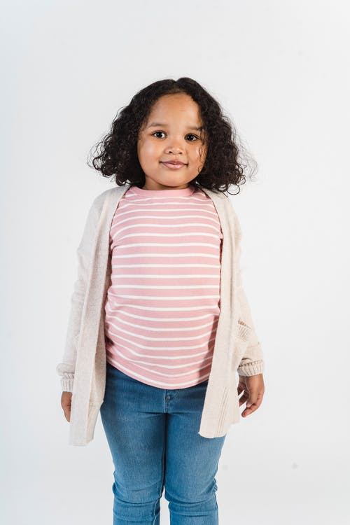 Positive black girl in casual outfit in studio
