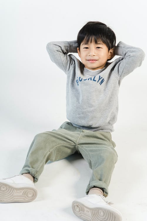 Cute little Asian boy in trendy casual clothing sitting on floor in studio
